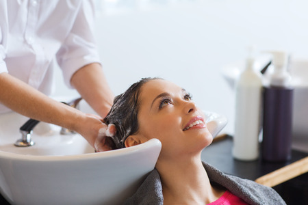 hair: beauty and people concept - happy young woman with hairdresser washing head at hair salon Stock Photo