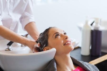 cabello: la belleza y el concepto de la gente - mujer joven feliz con la cabeza de lavado peluquero en el salón de pelo