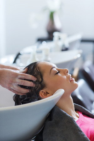 shampooing: beauty and people concept - happy young woman with hairdresser washing head at hair salon Stock Photo