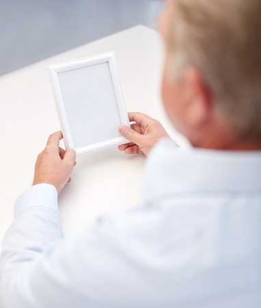 oldness: oldness, memories, loneliness and people concept - close up of old man holding blank photo frame