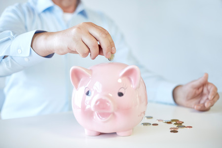 oldness: savings, oldness, business, people and banking concept - close up of senior man hands putting coins into piggy bank