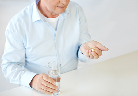 oldness: oldness, medicine, health care and people concept - close up of old man with pills and water glass