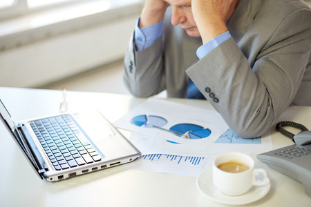 man in office: business, people, fail , technology and education concept - close up of stressed old man with laptop computer and papers in office Stock Photo