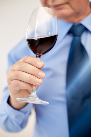degustating: profession, drinks, holidays and people concept - close up of senior man drinking red wine from glass