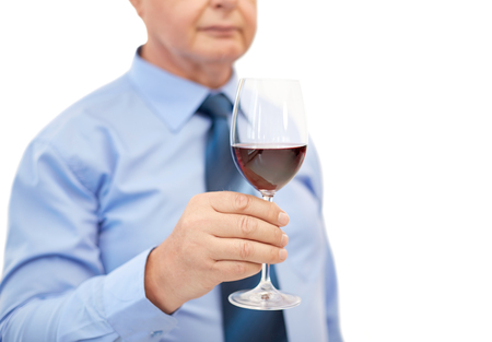 degustating: profession, winery, drinks, holidays and people concept - close up of senior man holding glass with red wine Stock Photo