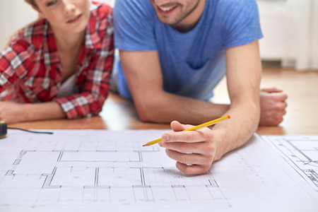 repair, building, renovation and people concept - close up of happy couple looking at blueprint at home