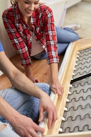 assembling: people, moving and furnishing concept - close up of couple assembling furniture at home Stock Photo