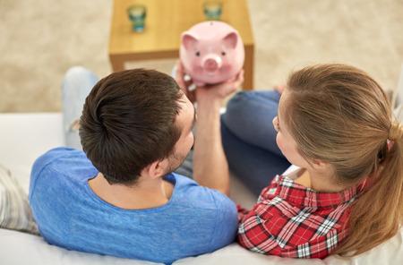geld, thuis, financiën en relaties concept - close-up van paar met piggy bank zittend op de sofa Stockfoto