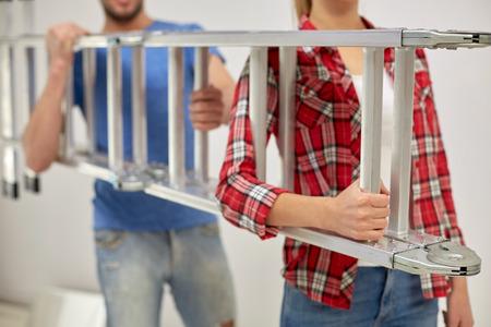 operarios trabajando: Concepto de las personas, la reparación, la construcción y el trabajo en equipo - Primer plano de pareja escalera llevar juntos en casa Foto de archivo