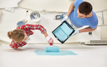 painting and decorating: repair, building, people, teamwork and renovation concept - couple with paint and roller painting wall at home