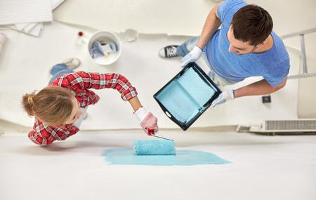 HOMBRE PINTANDO: reparación, construcción, personas, trabajo en equipo y la renovación concepto - pareja con pared de pintura de la pintura y el rodillo en casa