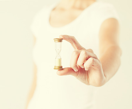 time out: close up of woman hand holding hourglass.