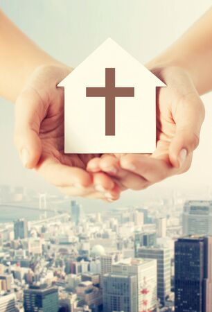 house of prayer: religion, christianity and charity concept - close up of woman hands holding paper house with christian cross symbol over city background