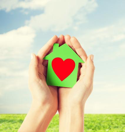 manos limpias: caridad, de bienes raíces y el concepto de casa de la familia - foto de primer plano de las manos femeninas que sostienen casa de papel verde con el corazón rojo