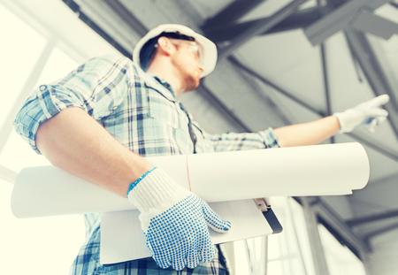 Architektur und Renovierungs-Konzept - ein Mann in Helm und Handschuhe mit Blaupause, die Richtung