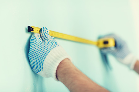 metric: repair, building and home concept - close up of male in gloves measuring wall with tape