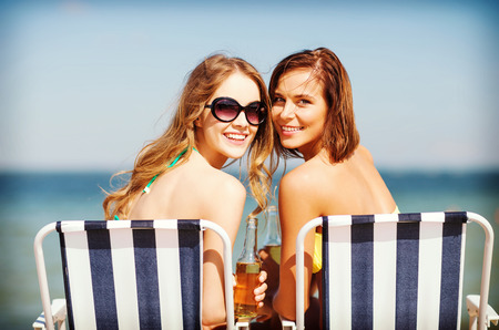 non alcoholic beer: summer holidays and vacation - girls in bikinis with drinks on the beach chairs