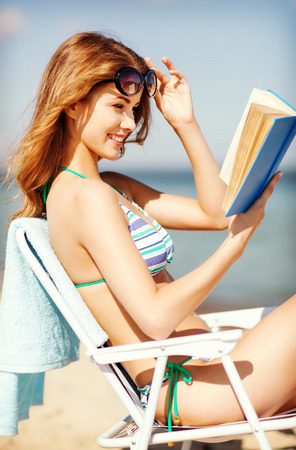 chilling: summer holidays and vacation - girl reading book on the beach chair