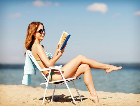暑假和假期的女孩在沙滩椅上看书