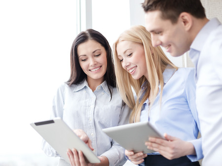 pcs: business and office concept - smiling business team working with tablet pcs in office