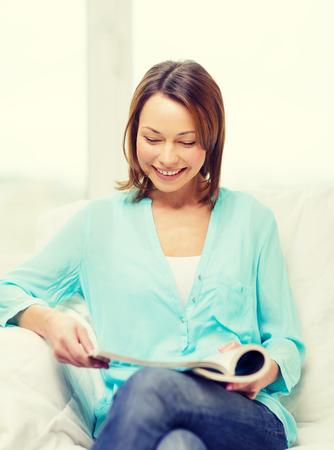 leasure: casa e leasure concept - donna sorridente lettura rivista a casa