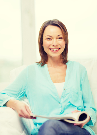 leasure: home and leasure concept - smiling woman reading magazine at home Stock Photo