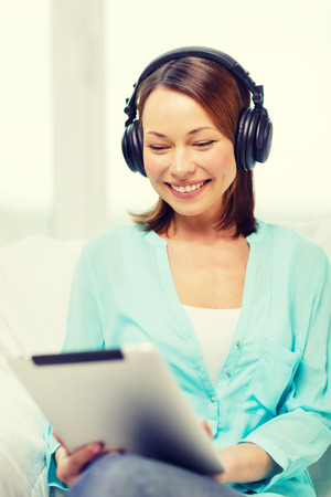 conputer: home, technology and internet concept - smiling woman sitting on the couch with tablet pc conputer and headphones at home