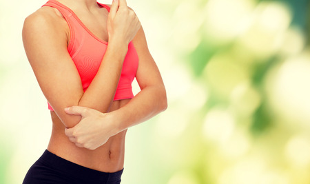elbow pain: healthcare, fitness and medicine concept - sporty woman with pain in elbow