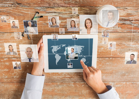 communities: business, people, international communication, headhunting and technology concept - close up of hands pointing finger to tablet pc computer screen with world map and internet contacts network on table Stock Photo