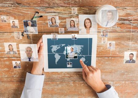 het bedrijfsleven, mensen, internationale communicatie, headhunting en technologie concept - close-up van de handen wijzende vinger naar tablet-pc computer scherm met wereldkaart en internet contacten netwerk op tafel
