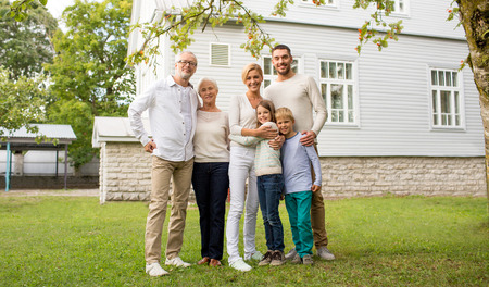 three generation: family, happiness, generation, home and people concept - happy family standing in front of house outdoors Stock Photo