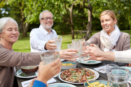 family dinner: family, generation, home, holidays and people concept - happy family having dinner and clinking glasses in summer garden