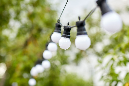 holiday lighting: decoration, illumination, electricity, holidays and lightning concept - close up of electric bulb garland hanging in rainy summer garden