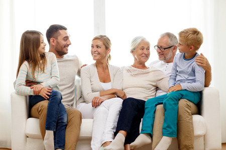multi age: family, happiness, generation and people concept - happy family sitting on couch at home