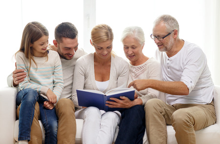 family, happiness, generation and people concept - happy family with book or photo album sitting on couch at home Imagens