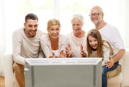 mujer viendo tv: familia, la felicidad, la generaci�n y la gente concepto - la familia feliz que se sienta en el sof� y viendo la televisi�n en casa