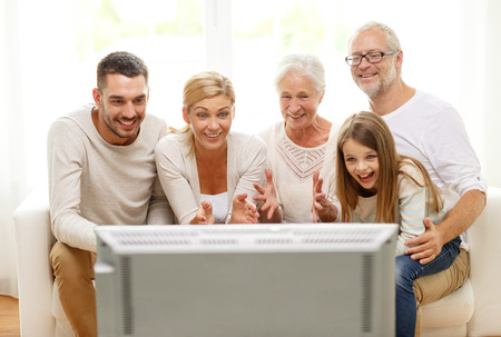 woman watching tv: family, happiness, generation and people concept - happy family sitting on sofa and watching tv at home Stock Photo