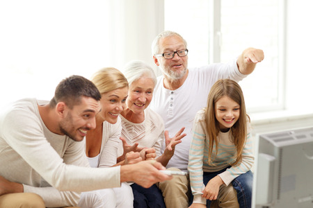 family support: family, happiness, generation and people concept - happy family sitting on sofa and watching tv at home Stock Photo