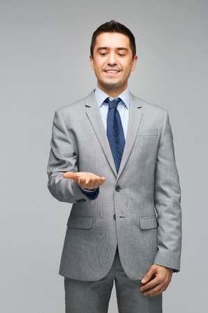 business, people, advertisement and office concept - happy businessman in suit showing or holding something imaginary on empty palms photo