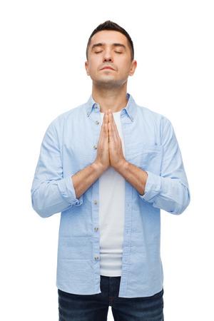 manos orando: la fe en Dios, la religión y la gente concepto - hombre feliz con los ojos cerrados rezando Foto de archivo