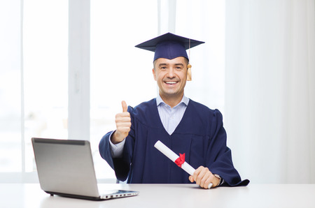 education, graduation, business, technology and people concept - happy adult student in mortarboard with diploma and laptop computer showing thumbs up home or office