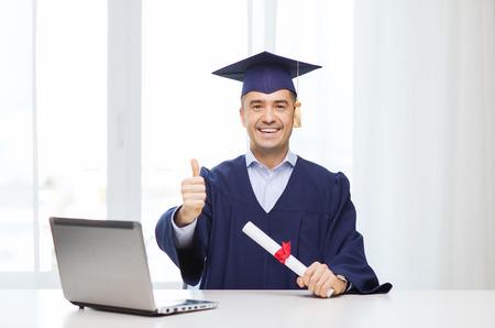 graduacion de universidad: la educación, de la graduación, los negocios, la tecnología y la gente concepto - estudiante adulto feliz en birrete con diploma y de la computadora portátil que muestra los pulgares para arriba casa u oficina