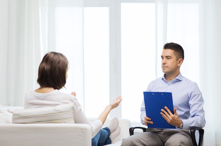 unhealthy living: medicine, health care and people concept - doctor with clipboard and young woman meeting at home visit