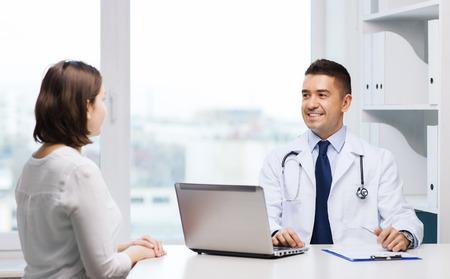 의학, 건강 관리와 사람들이 개념 - 노트북 컴퓨터와 병원에서 젊은 여성 회의와 웃는 의사