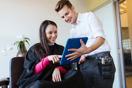 man long hair: beauty, hairstyle, technology and people concept - happy young woman and stylist with tablet pc computer at salon