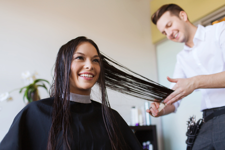 beauty, hairstyle and people concept - happy young woman and hairdresser cutting hair tips at salon