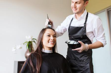 schoonheid en mensen concept - gelukkige jonge vrouw met kapper kleuren haren bij salon Stockfoto