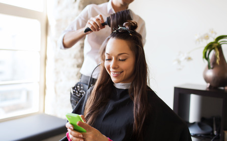 beauty, hairstyle and people concept - happy young woman with smartphone and hairdresser making hair styling at salon Stockfoto