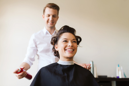salon: beauty, hairstyle and people concept - happy young woman with hairdresser with hair spray fixating hairdo at salon