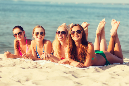relaxed woman: summer vacation, holidays, travel and people concept - group of smiling young women in sunglasses lying on beach